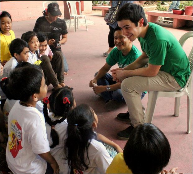 David Archuleta reads to childfund kids cred Childfund.  David is wearing a Green Shirt and all the children are smiling